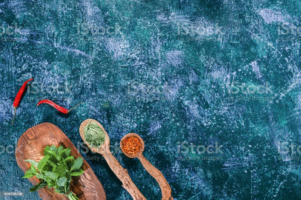 Fresh lemon balm on wooden plate and dried spices in wooden spoons...
