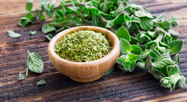 Fresh and dried oregano herb on wooden background Fresh and dried oregano herb on wooden background oregano stock pictures, royalty-free photos & images