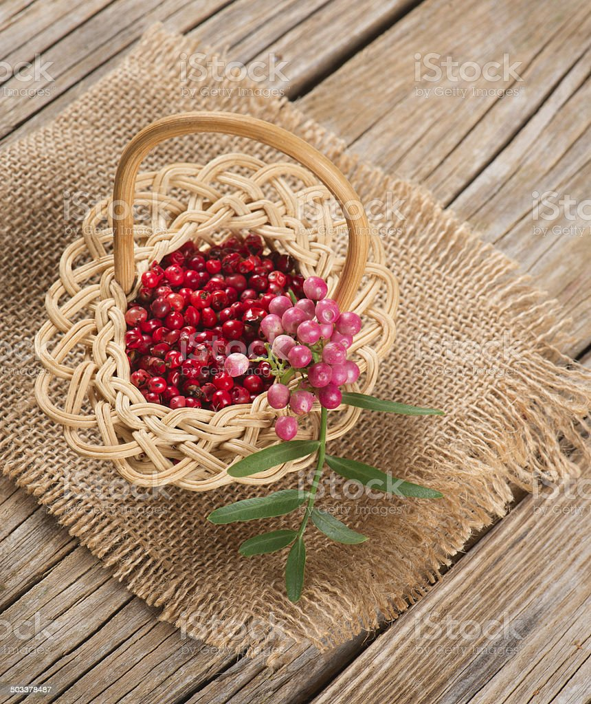 fresh and dried pink pepper in a small basket stock photo