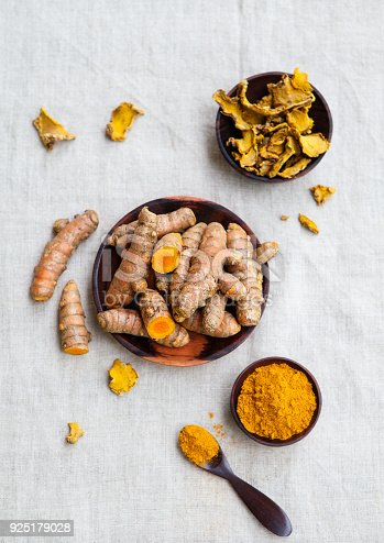 istock Fresh and dried turmeric roots in a wooden bowl. Grey textile background. Top view. 925179028