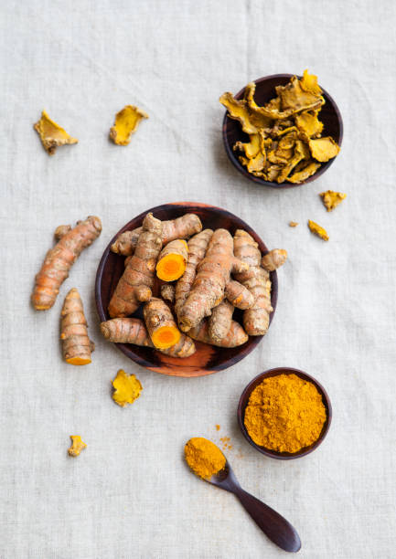 Fresh and dried turmeric roots in a wooden bowl. Grey textile background. Top view. stock photo