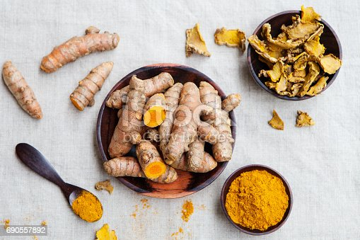 istock Fresh and dried turmeric roots in a wooden bowl 690557892