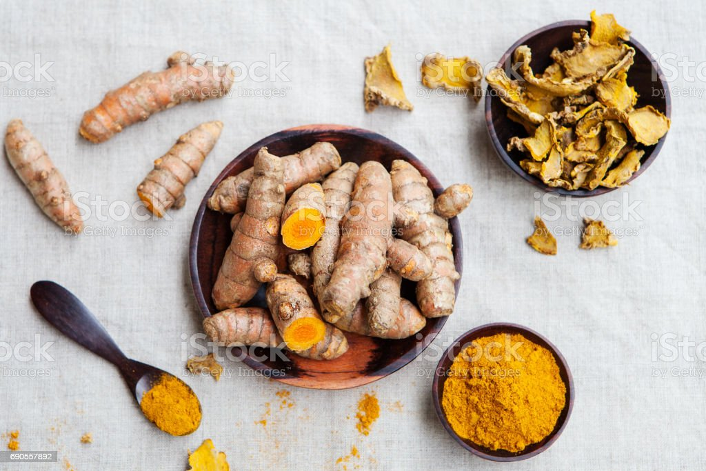 Fresh and dried turmeric roots in a wooden bowl stock photo