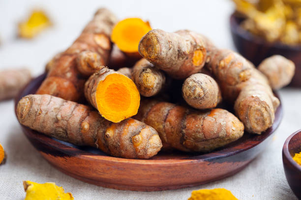Fresh and dried turmeric roots in a wooden bowl. stock photo