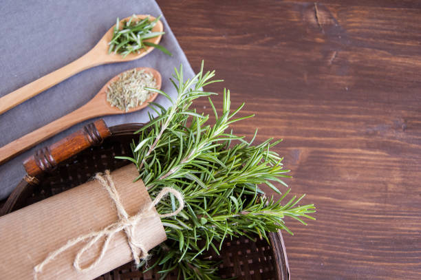 Fresh and dry rosemary on a wooden background Fresh and dry rosemary on a wooden background rosmarino stock pictures, royalty-free photos & images