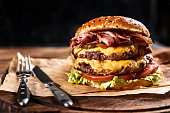 Fresh and juicy hamburger on a paper pillow with beer on a wooden table. Dark background, traditional american food. Junk food