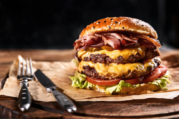 Fresh and juicy hamburger on a paper pillow with beer on a wooden table. Dark background, traditional american food. Junk food stock photo