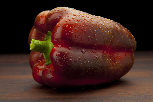 Fresh and raw red pepper with drops of water on wooden board and black background