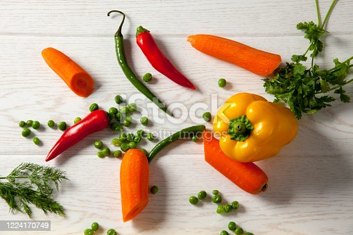 Green pepper, red hot pepper and yellow big pepper. Dill, peas and parsley with wood pattern and over white background