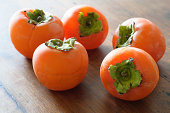 istock Fresh and Ripe Persimmon fruit backlit on old wooden table 170131861