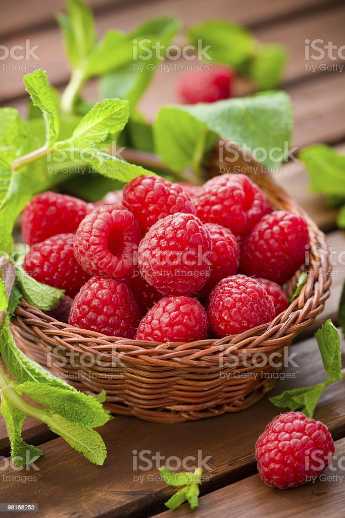 Fresh and ripened raspberries with greens in small basket royalty-free stock photo