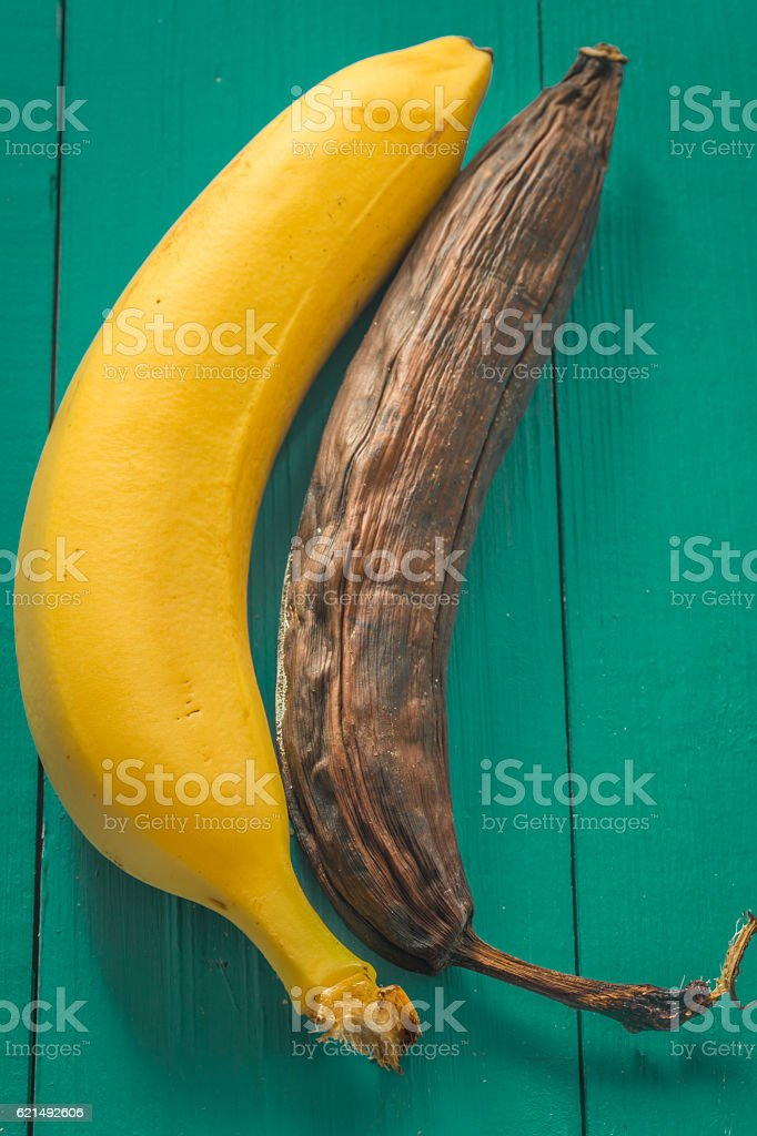 fresh and rotten banana on wooden background Lizenzfreies stock-foto