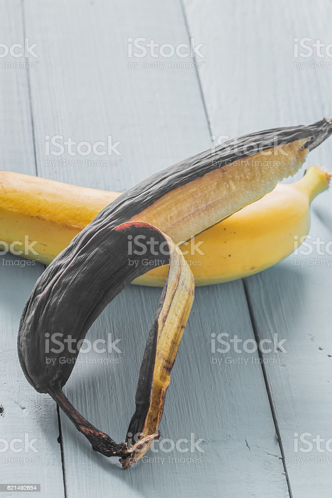 fresh and rotten banana on wooden background foto stock royalty-free