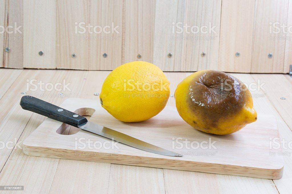 Fresh and rotten lemon put on chopping block stock photo