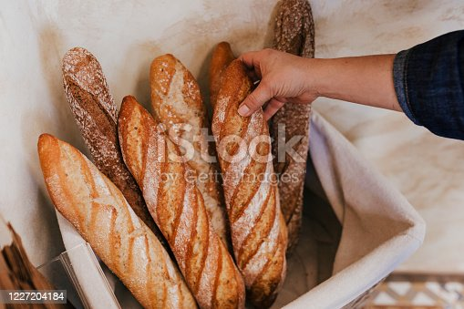 Fresh and warm. close up woman hand holding fresh and warm bread just from the oven. Bakery concept