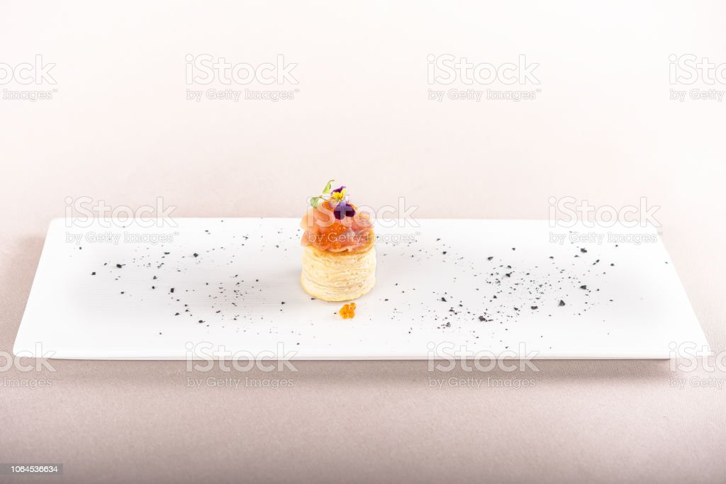 Fresh appetizer with smoked salmon and caviar,  on pastry,  decorated with eatable purple  flower and green leaf,  placed on white plate,  light background,  isolated stock photo