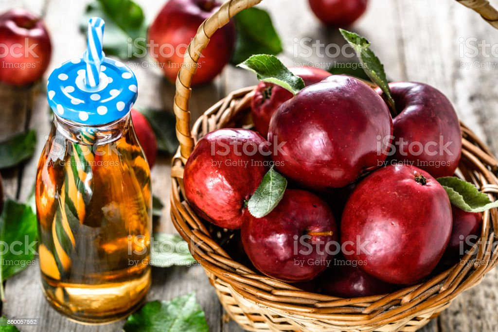 Fresh apple juice in the bottle - detox drink with red apples on wooden table, organic food and healthy lifestyle concept stock photo