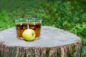 The one glass of fresh apple juice with apple fruit on a wooden stump outdoors. Green background