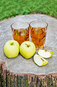 The two glasses of fresh apple juice with apples fruit on a wooden stump outdoors. Green background