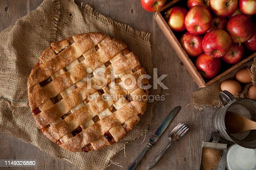 Fresh apple pie with ingredients on a wood background
