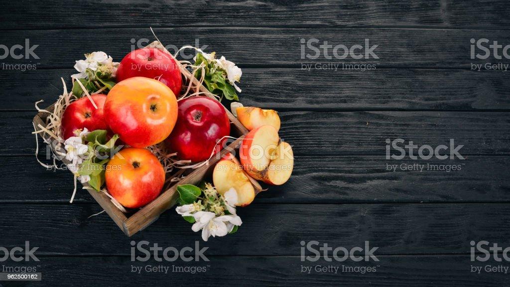 Maçãs frescas em uma cesta de madeira. Sobre um fundo de madeira. Vista superior. Copie o espaço. - Foto de stock de Agricultura royalty-free