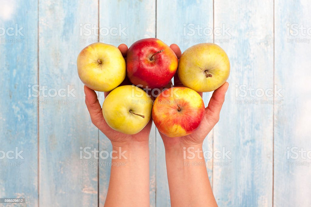 Fresh apples in hand and on blue wooden table photo libre de droits