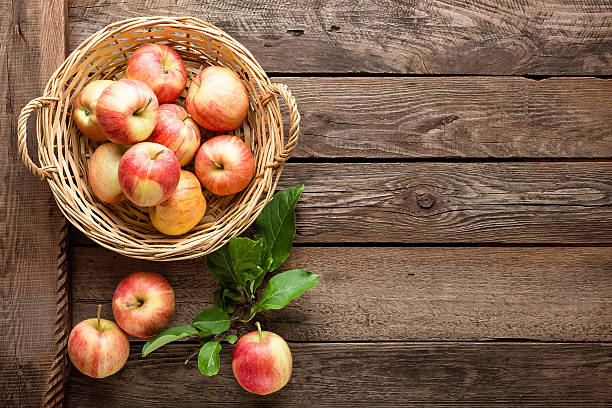 fresh apples in wicker basket on wooden table - Photo