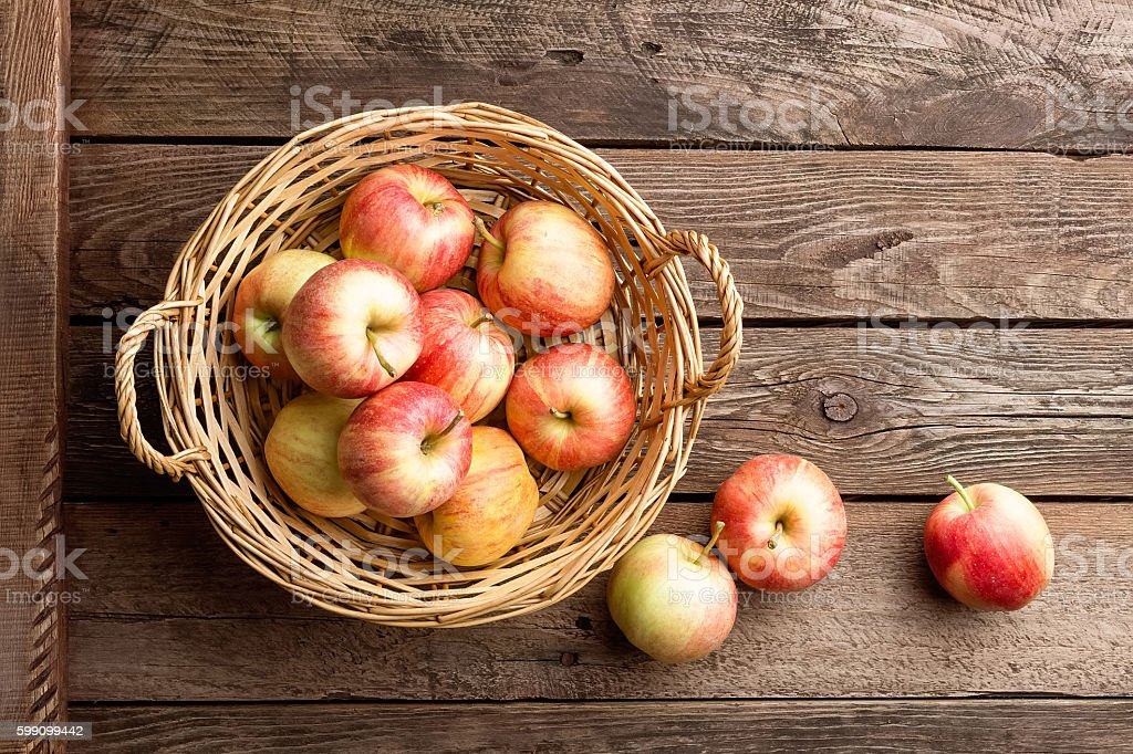 fresh apples in wicker basket on wooden table – Foto
