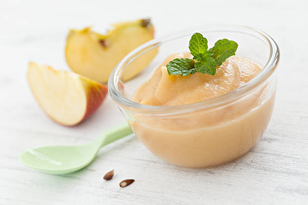 Fresh applesauce in a bowl with apples and a spoon stock photo