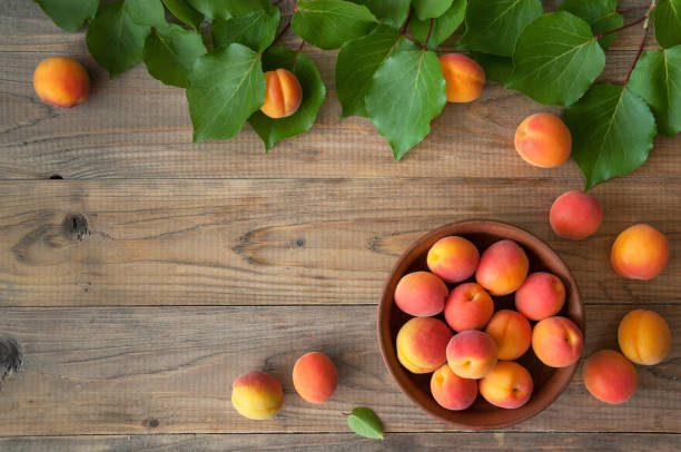 Fresh apricots with leaves in a bowl on a wooden background stock photo