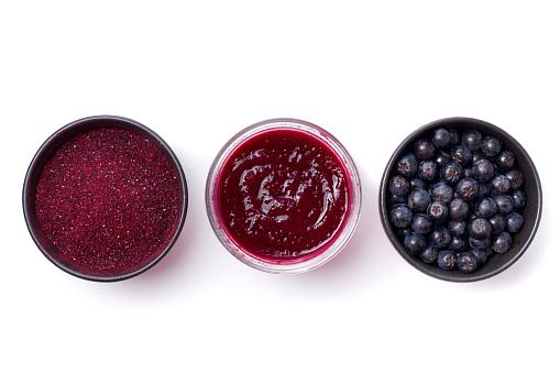 Fresh Aronia berries, powder and jam on white background