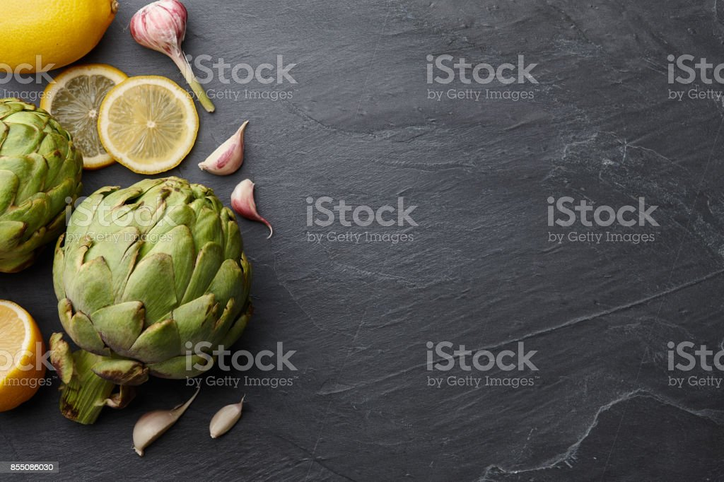 Fresh artichokes with lemons and garlic on stone background stock photo