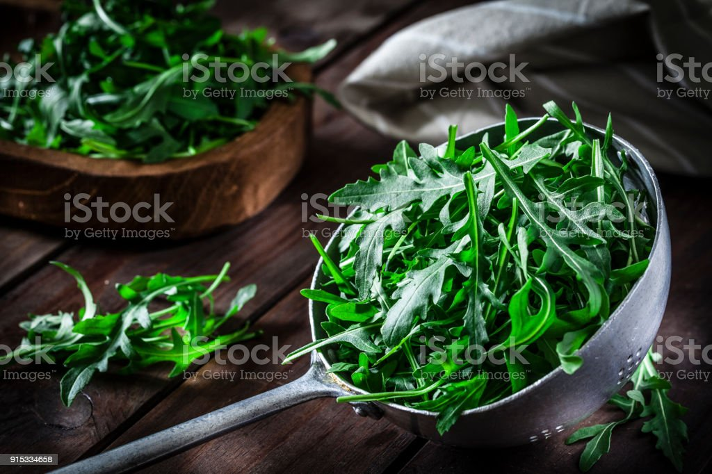 Fresh arugula in an old metal colander stock photo