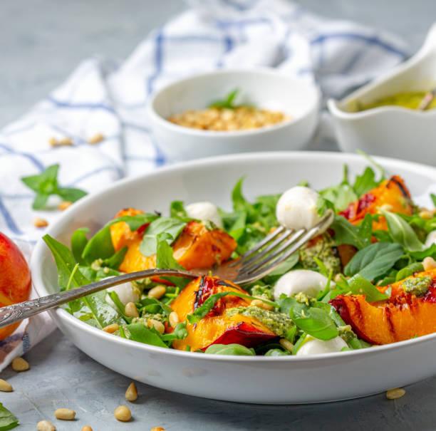 Fresh arugula salad with nectarines and pesto. stock photo