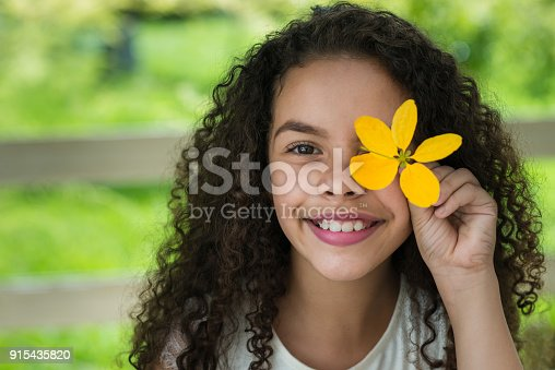 Beautiful litlle girl holding a yellow flower on his face.