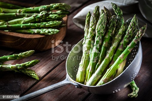 Fresh organic asparagus in an old metal colander shot on rustic wooden table. This vegetable is considered a healthy salad ingredient. Predominant colors are green and brown. Low key DSRL studio photo taken with Canon EOS 5D Mk II and Canon EF 100mm f/2.8L Macro IS USM
