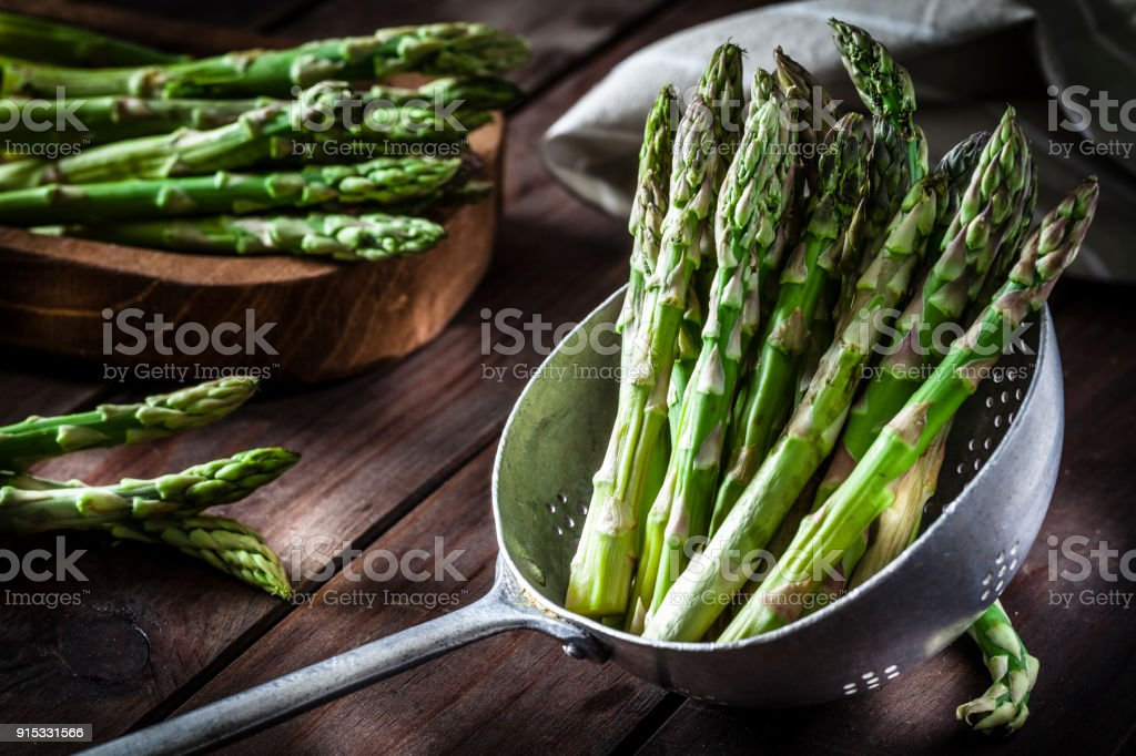 Fresh asparagus in an old metal colander stock photo
