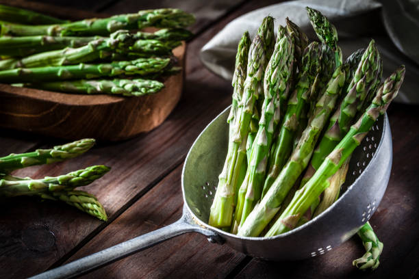 fresh asparagus in an old metal colander - asparagus stock pictures, royalty-free photos & images