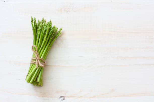 Fresh asparagus on white wood background stock photo