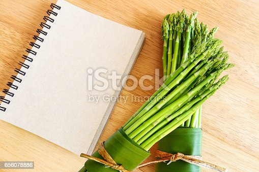 istock Fresh asparagus on wooden background and blank diary book. 656078886