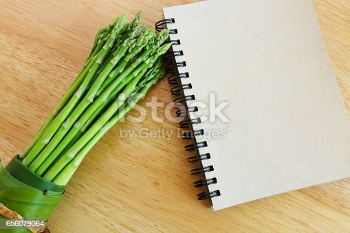 istock Fresh asparagus on wooden background and blank diary book. 656079064