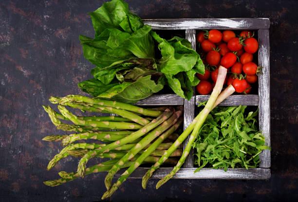 frischer spargel, tomaten. rucola und kopfsalat in holzkiste auf dunklem hintergrund - spargel vegan stock-fotos und bilder