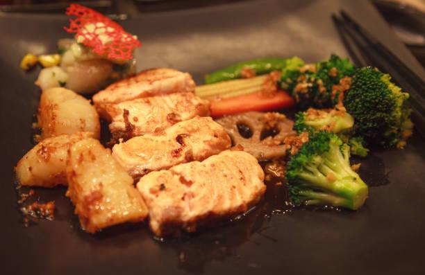 frisches, assorted seafood, lachsfillet, scallop und gemüse-teppanyaki grill (japanische küche, die einen eisengrudel oder eine heiße bratpfanne zum kochen von speisen verwendet) im traditionellen steakhouse. konzept für lebensmittelkochen - teppan yaki grill stock-fotos und bilder