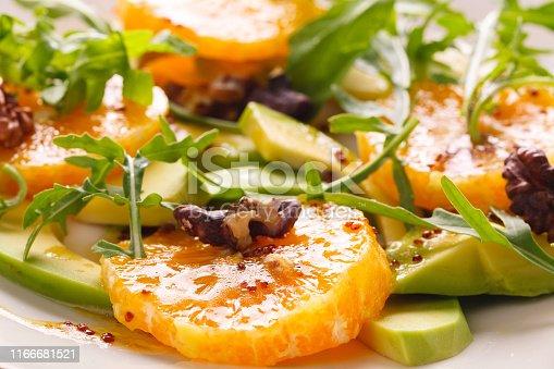 fresh summer salad of avocado, oranges, arugula and nuts on a beige plate. Salad for restaurant or cafe.