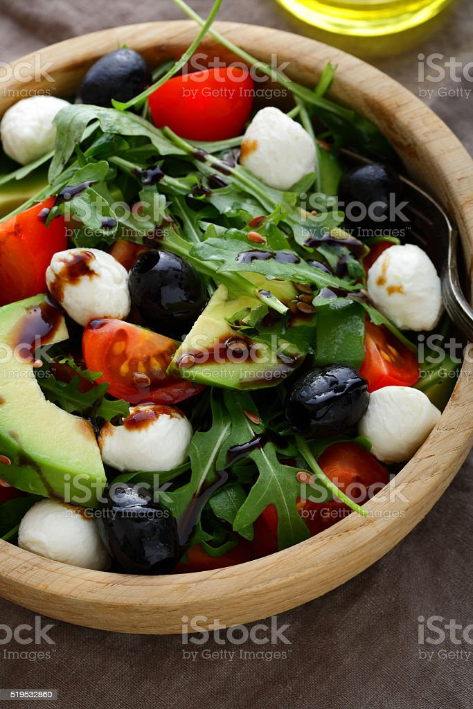 Fresh Avocado Salad with cherry tomatoes, olive, mozzarella and arugula stock photo