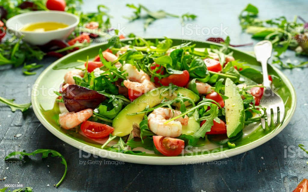 Fresh Avocado, shrimps salad with lettuce green mix, cherry tomatoes, herbs and olive oil, lemon dressing. healthy food stock photo