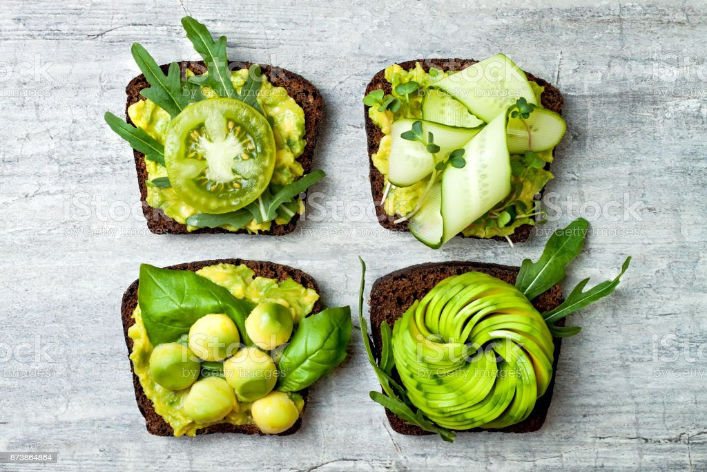 Fresh avocado toasts with different toppings. Healthy vegetarian breakfast with rye wholegrain sandwiches stock photo