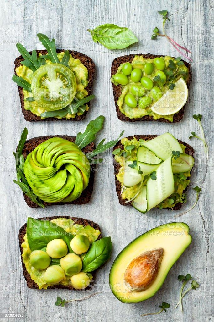 Frische Avocado-Toast mit verschiedenen Belägen. Gesunde vegetarische Frühstück mit Roggen Vollkorn sandwiches – Foto