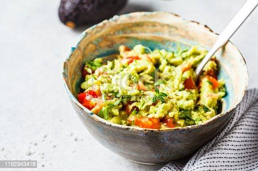 Fresh avocado tomato guacamole in a bowl. Healthy vegan food concept.
