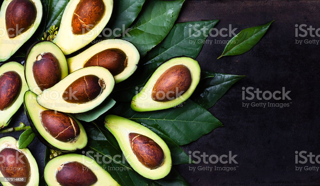 Fresh avocado with leaves on black background stock photo